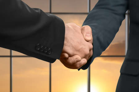 realtionship: Managers shake hands at sunset. Stock Photo