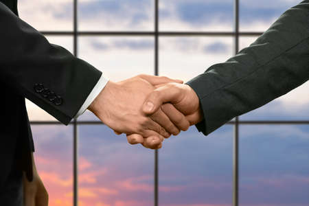 realtionship: Businessman shake hands at sunset