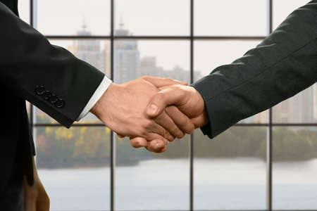 realtionship: Businessmen shake hands at daytime. Stock Photo