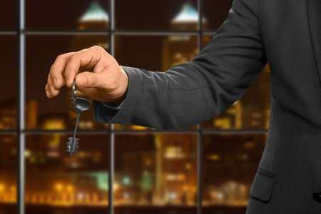hideout: Male realtor gives apartment key. Night office worker holding key. Choose the right door. Knock and open.
