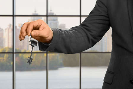 hideout: Businessman with key beside window. Adult man holding office key. The new apartment is yours. Daytime in realty agency. Stock Photo