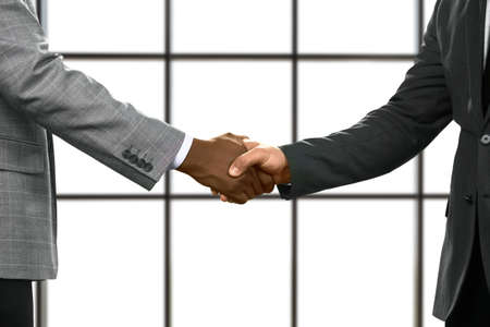 realtionship: Businessmen shake hands in headquarters.