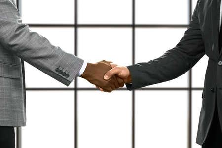 Les hommes d'affaires se serrent la main au siège. Banque d'images