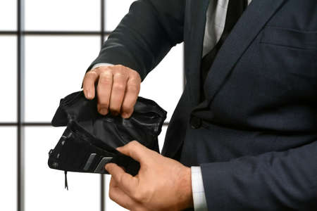 truly: Businessmans hands with empty wallet. Office employee holding empty wallet. Waiting for salary. Truly sad situation.