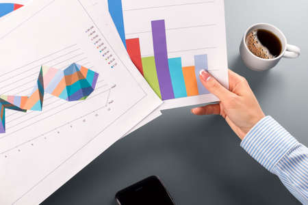 clerks: Female clerks hands holding charts. Stock Photo