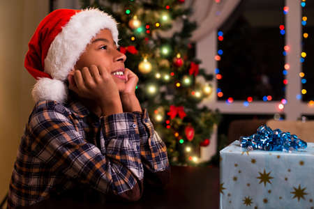 unpack: Smiling black kid on Christmas. Boy in Santa hat smiling. Cant wait to unpack presents. Atmosphere of Christmas eve.