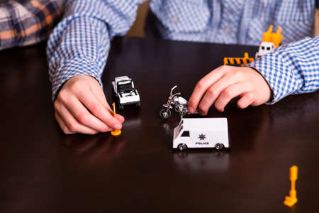 a white police motorcycle: Boys hand moves toy vehicle. Kid playing with toy cars. Re-creating work of police. Law enforcement in miniature.