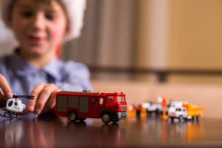Boy plays with toy helicopter. Kid with toy police helicopter. Law enforcement and fire department. Always ready to act. Stock Photo