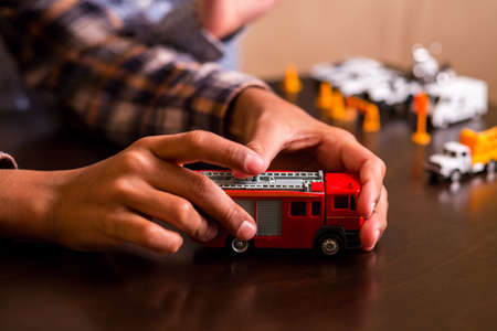 a white police motorcycle: Kid playing with fire truck. Childs red toy fire truck. We should hurry. Heroes at your service. Stock Photo