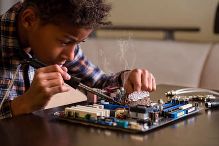 Afro boy fixing motherboard. Black kid repairs motherboard. Few touches here and there. Everything by the book.