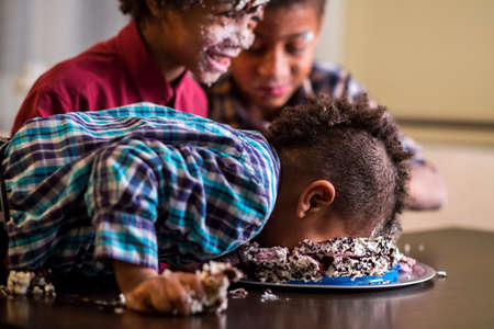 smashing: Afro boys face smashing cake. Kid smashes cake with face. Have a small bite. Heres a true gourmet. Stock Photo