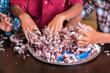 smashing: Boys smashing cake with hands. Three childrens hands smash cake. This is the end. Weve done everything we could.