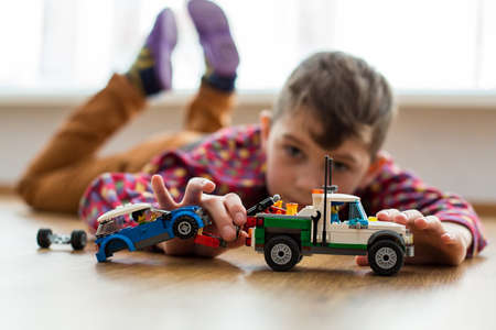 Boy plays with toy cars. Kid playing on the floor. Child's daytime fun. Happy to be at home. Banque d'images