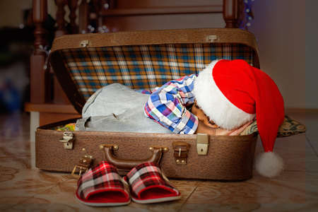 come up: Afro kid sleeping inside suitcase. Little Santa sleeping in suitcase. Time to wake up. Holiday has come.