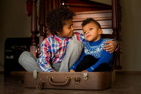 smile please: Friendly boys sit inside suitcase. Two friendly-looking afro kids. Look at me, brother. Smile for the photo, please.