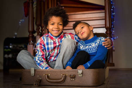 look after: Smiling kids sit inside suitcase. Joyful afro boys near staircase. Happy to have a brother. Look after those you love. Stock Photo