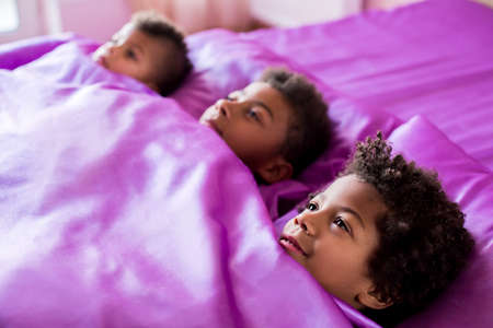 Three black boys in bed. Afro boys on purple bed. Time to go to school. Its breakfast time.