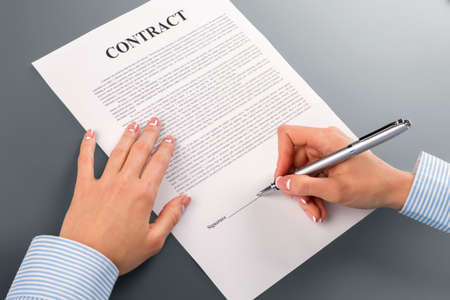 risky: Female hand signs loan contract. Womans hand signing loan contract. I have no choice. This is very risky. Stock Photo