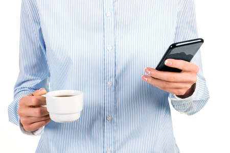 fresh news: Womans tea cup and cellphone. Lady holding smartphone and cup. Reading fresh news at work. Im glad its fully charged.