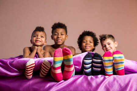 boy sitting: Happy boys in colorful socks. Cheerful boys sitting on bed. Cherish your friendship. When we were young.
