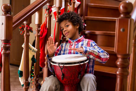 afro: Young afro drummer on stairs. Friendly afro child with drum. Playing djembe like a pro. Free Christmas concert.