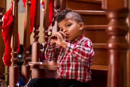 te negro: chico negro que toca la flauta. Kid toca la flauta en las escaleras. Uno tiene que tener la habilidad. ¿Se puede impresionar a la audiencia. Foto de archivo