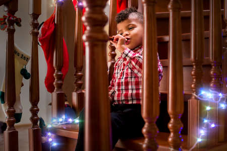 tonality: Kid playing flute on stairs. Boy with flute on Christmas. For all the good things. Music always brings joy. Stock Photo