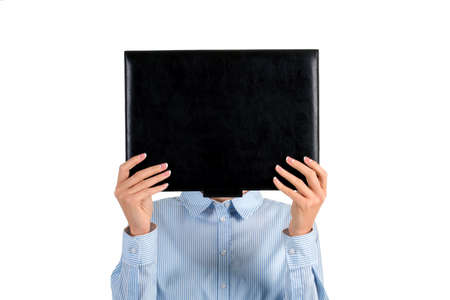 face covered: Ladys face covered with folder. Woman holding black leather folder. Mysterious girl covering her face. Intriguing photo of a woman. Stock Photo