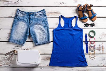 여자의 탱크 탑과 반바지. 나무 배경에 여성 옷장. 라이트 여성 여름 옷. 액세서리와 함께 좋은 여름 옷. 스톡 콘텐츠