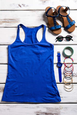 woman's clothing: Female tank top and sandals. Womans clothing on wooden shelf. Simple top and nice accessories. Simple clothing for woman.