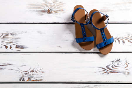 informal clothing: Close-up of womans blue sandals. Female sandals on wooden shelf. Summer footwear with small buckle. Girls shoes for summer. Stock Photo