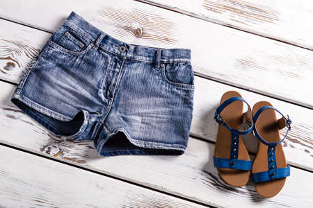 womans clothing: Ladys blue shorts and sandals. Womans clothing on white shelf. Short jeans shorts with sandals. Girls summer collection. Stock Photo