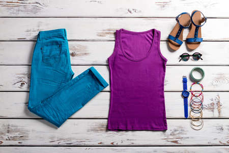 Blue pants and purple top. Colorful clothes on wooden background. Bright-colored outfit for summer. Simple colorful clothes for women.
