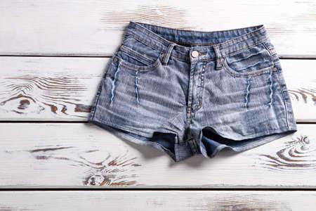 denim shorts: Female vintage denim shorts. Shorts on white wooden background. Simple denim shorts for women. Classic denim garment. Stock Photo