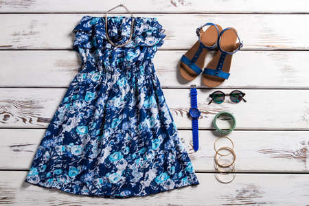 womans clothing: Womans vintage dress and sandals. Vintage clothing on wooden background. Strapless dress with flower pattern. Vintage blue flower pattern. Stock Photo