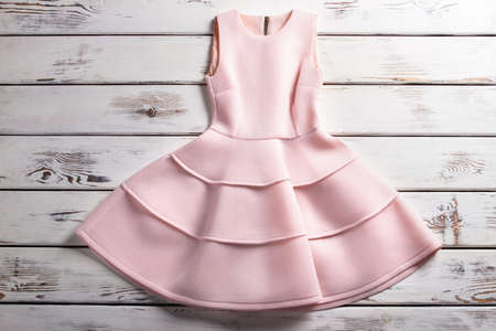 woman's clothing: Salmon cocktail dress with zipper. Dress on stores showcase. Womans delicate piece of clothing. Elegant dress with silk lining.