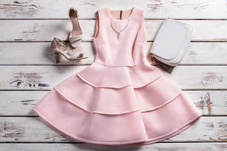 Kleid mit Schuhen und Schmuck. Maßgeschneiderte Kleidung auf dem Regal. Frau Kleidung und Accessoires. Abend Sammlung in Lookbook.