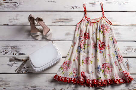 Floral sarafan and footwear. Sarafan and shoes on showcase. Woman's simple outfit for summer. Garment of light fabric.