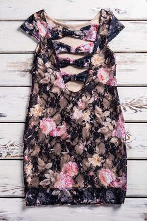 neckline: Floral dress with deep neckline. Dark dress on wooden background. Dark dress with silk lining. Womans transparent piece of clothing. Stock Photo