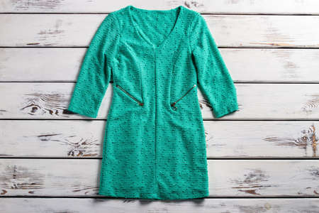 informal clothing: Turquoise dress with pockets. Dress laying on wooden table. V-neck turquoise dress. Womans long sleeve garment. Stock Photo