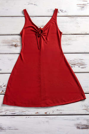 Red dress with keyhole neckline. Red dress laying on showcase. Smooth stretch dress. Garment on white wooden shelf.