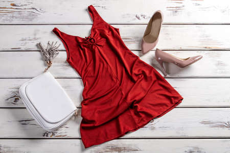 garments: Red dress with clutch bag. Clothes and footwear on table. Fashionable garments for modern women. City girls outfit.