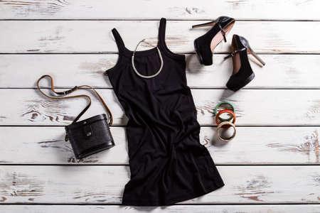 검은 드레스, 신발, 보석. 테이블에 흑인 여성 옷. 지갑 매력적인 어두운 옷. 레트로 지갑과 현대 의류.