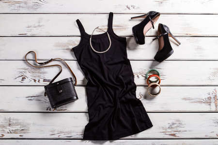Zwarte jurk, schoenen en sieraden. Zwarte vrouwelijke outfit op tafel. Glamorous donkere kleding met portemonnee. Retro beurs en moderne kleding. Stockfoto