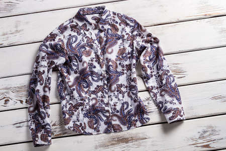 long sleeve: Ladys long sleeve floral shirt. Shirt on white wooden shelf. New garment on old table. Shirt laying on white floor.
