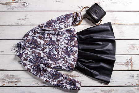 table skirt: Black skirt with floral shirt. Elegant clothes on white table. Leather skirt and small purse. Retro-looking handbag and clothes. Stock Photo