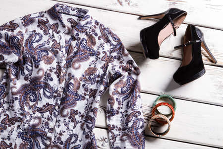 woman's clothing: Floral shirt and coloful bracelets. Womans clothing on wooden floor. Trendy footwear and nice shirt. Style of modern women.