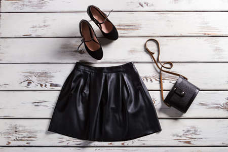 leather skirt: Leather skirt and suede shoes. Skirt and footwear on shelf. Fashionable clothes for modrn girls. Ladys trendy evening clothes. Stock Photo