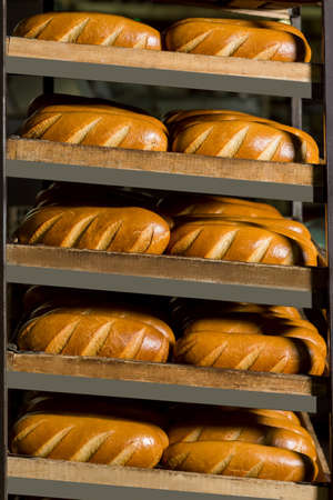 bakery store: Fresh golden bread on the shelves. Delicious crisp bread at the bakery. Delivery bread in store.