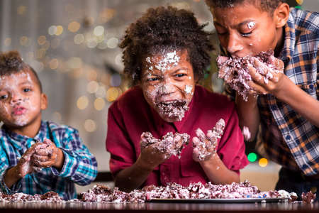 disobedient: Afro kids greedily eating cake. Three boys devour small cake. Welcome to our humble party. Celebrating together is fun.